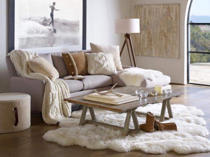 une image cocooning qu'on dirait sortie d'un catalogue déco scandinave, avec un tapis douillet, un canapé sublimé de coussins cocooning dépareillés et un grand tableau mural de poster photo