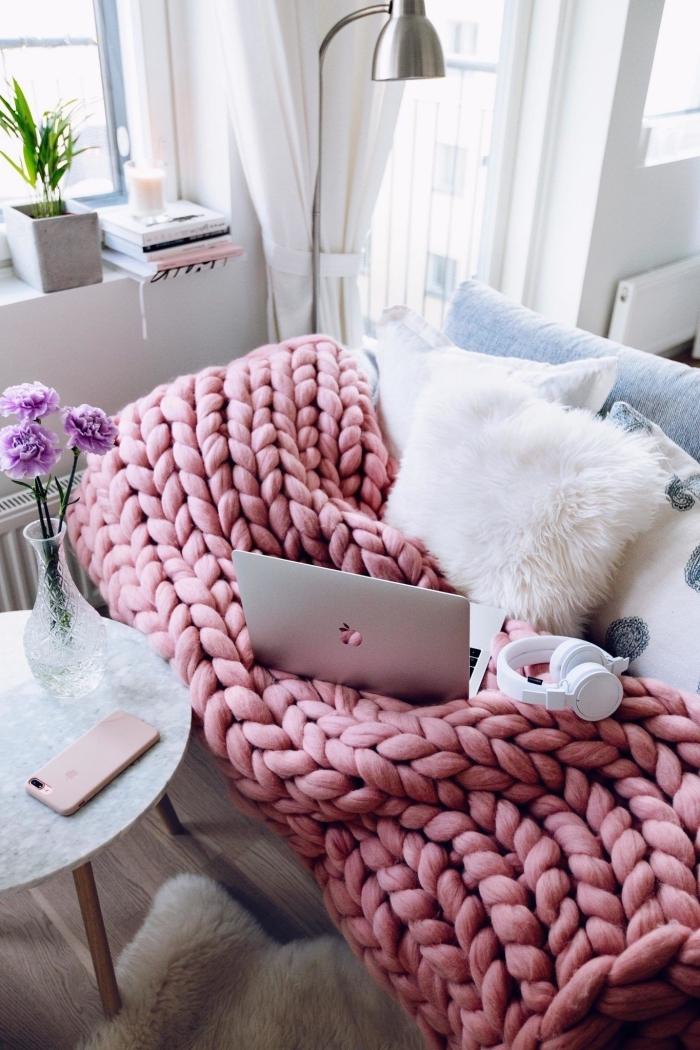 canapé transformé en petit coin cosy avec un coussin cocooning en fourrure blanche et un plaid grosse maille couleur rose bonbon
