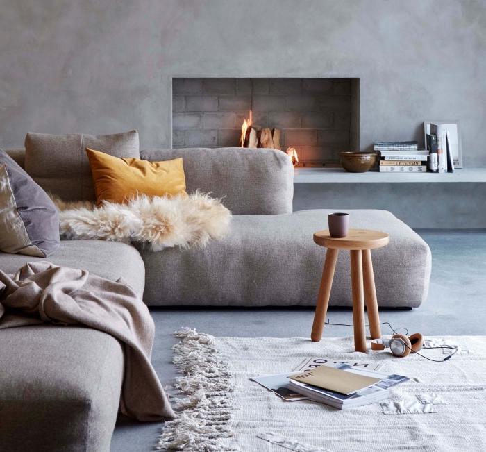 de la simplicité et de la douceur dans ce salon gris aux murs effet béton avec une cheminée encastrée et un grand canapé cosy