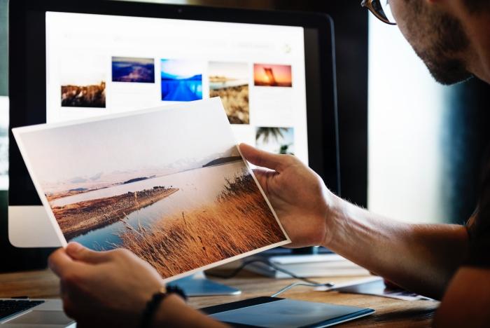 un homme tenant un tirage photo représentant un joli paysage naturel paisible, idées de déco murale avec des posters photo en formats variés