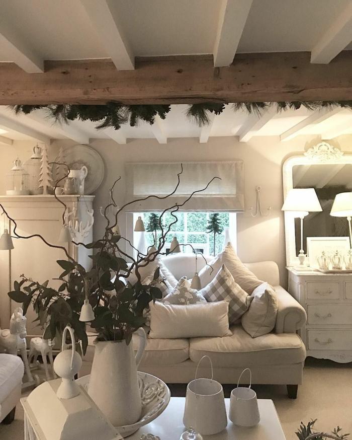 salon en bois et blanc, carafe blanche et déco végétale, sofa crème, placards blancs, statuettes de chevaux blancs