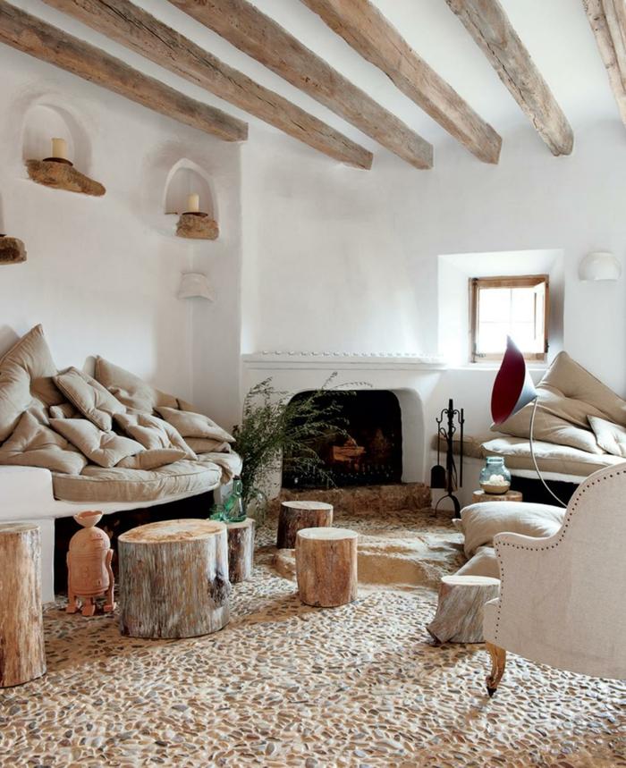 idée déco amenagement maison de campagne, poutres en bois brut, sol mosaique, troncs d'arbre, plusieurs coussins empilés, petites niches murales