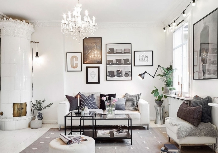deco salon scandinave moderne avec une poêle à bois d'angme, un canapé blanc décoré d'une multitude de coussins et un mur de cadre tendance