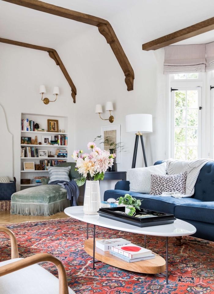salon vintage et bohème chic avec un tapis persan, un canapé bleu pétrole et une table basse ovale en métal, bois et marbre, ambiance cocooning et authentique avec des poutres apparentes au plafond et une méridienne vintage en velours