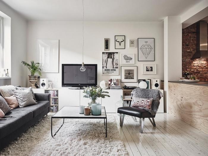 ambiance déco scandinave de style hygge avec un tapis cocooning, un canapé confortable et un parquet de bois blanchi qui illumine l'intérieur