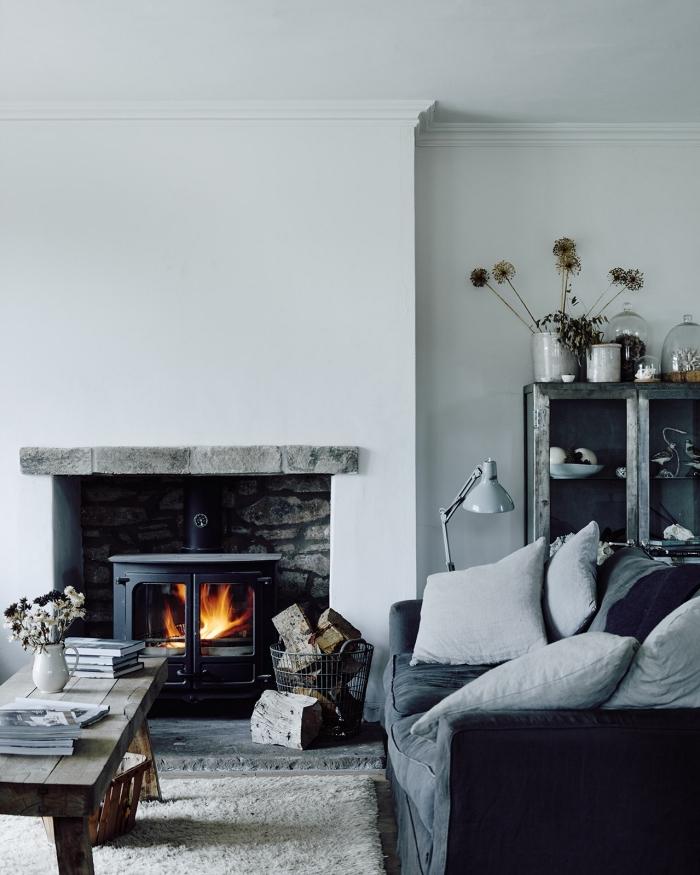 deco salon gris de style rustique chic aux accents industriels avec un insert dans une cheminée à foyer ouvert, une table en bois rustique et un canapé gris moelleux