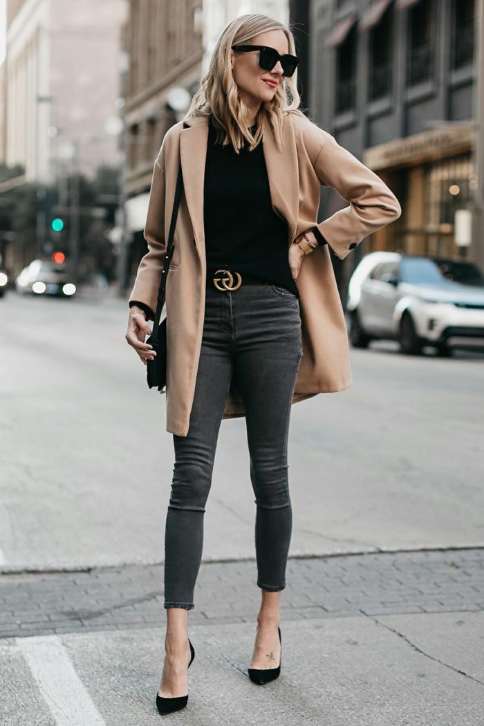 jolie femme blonde, jeans skinny, ceinture de marque populaire, pull noir, escarpins élégants