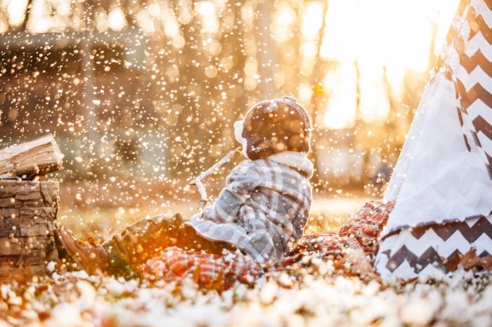 photo de la neige qui tombe au lever du soleil, fond d'écran gratuit avec un enfant qui joue dans la neige