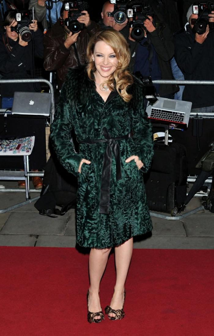 Kylie Minogue avec une veste en fourrure synthétique longue aux genoux, sandales escarpins aux papillons