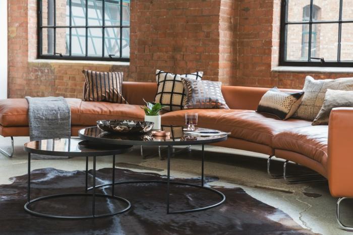 tapis peau de bête dans un slaon à esprit industriel, murs en briques, canapés design courbé en cuir marron, deux tables gigognes