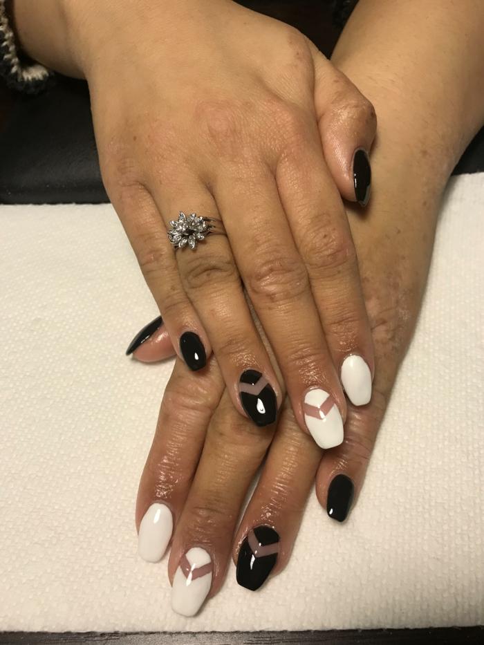 bague en argent, doigts manucurés en noir et blanc au motif géométrique, manucure espace négatif