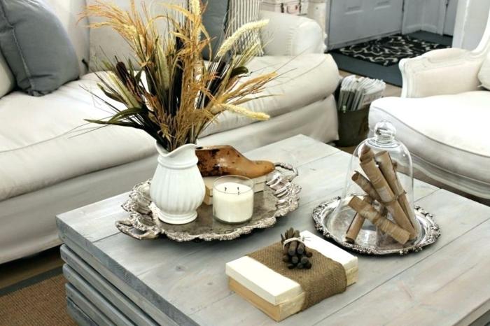 table de salon carrée, vase blanc avec des fleurs sèches, plateaux d'argent, bougie blanche, grand couvercle en verre