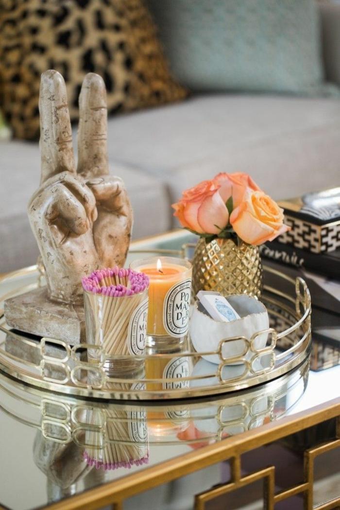 sculpture originale, vase avec des fleurs, bougie allumée orange, plateau design métallique, coussin motif animal