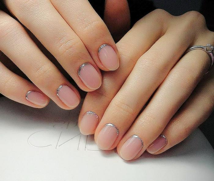 doigts manucurés, nail art rose, bague d'argent, lunule décorée avec un demi cercle argenté