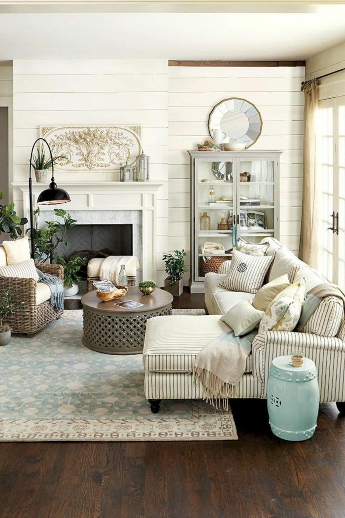 tapis bleu, table basse ronde, sofa d'angle beige, miroir fenêtre, buffet blanc, lambris mural blanc, cheminée, salon déco campagne chic