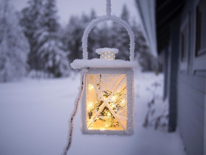 joli fond d écran noel, image lanterne allumée devant une maison de forêt enneigée, idée photo gratuite sur thème hiver