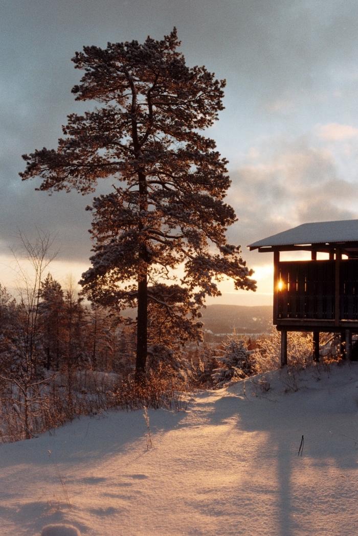 idée fond d écran noel, photo sur le thème hiver avec coucher du soleil au-dessus des montagnes et une maison en bois