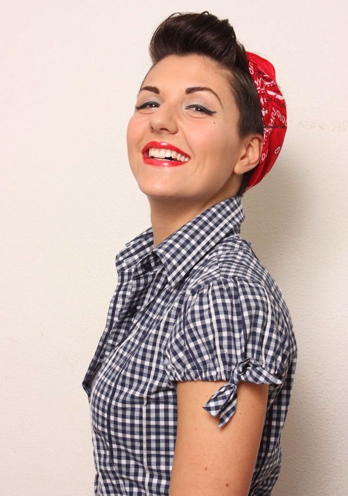 look de pin up style serveuse de dinner avec chemise à carreaux et bandana rouge dans les cheveux et coiffure rockabilly banane enroulée