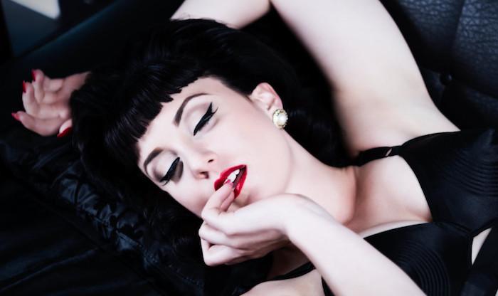 femme brune look pin up avec coiffure retro à frange et maquillage année 50 eye liner noir et rouge levres