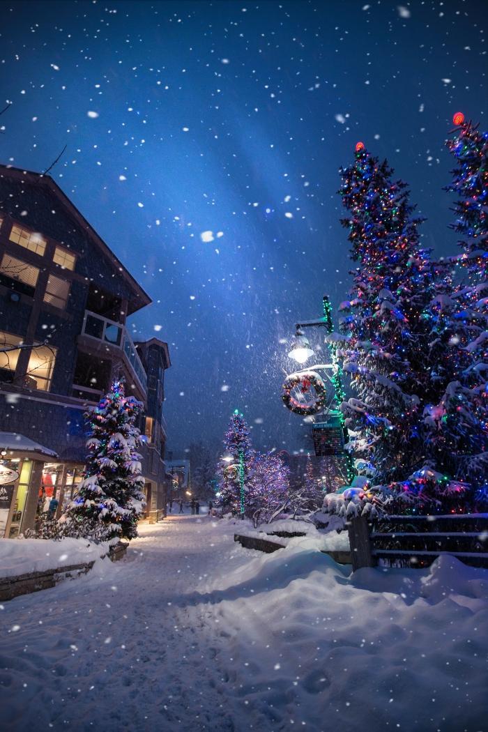 image de noel gratuite a telecharger, photo chute de neige dans un village décoré pour la fête de noel avec guirlandes et lumières