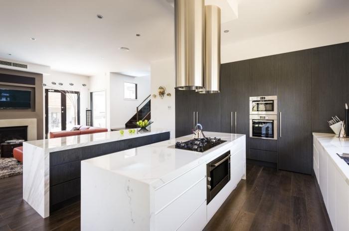 aménagement cuisine ouverte vers le salon avec deux îlots, déco de cuisine en blanc et noir avec finition or