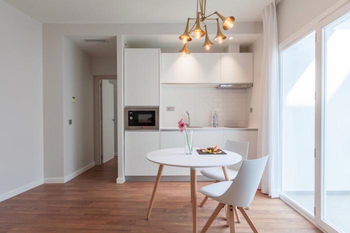aménagement cuisine ouverte en blanc et bois avec table a manger ronde, modèle de crédence cuisine tendance carreaux briques blanches