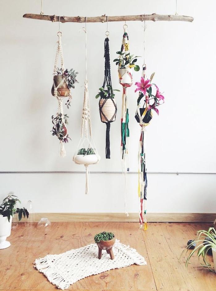 pots de fleurs suspendus en macramé sur une branche de bois flotté, parquet bois clair, petit tapis macramé, murs blancs