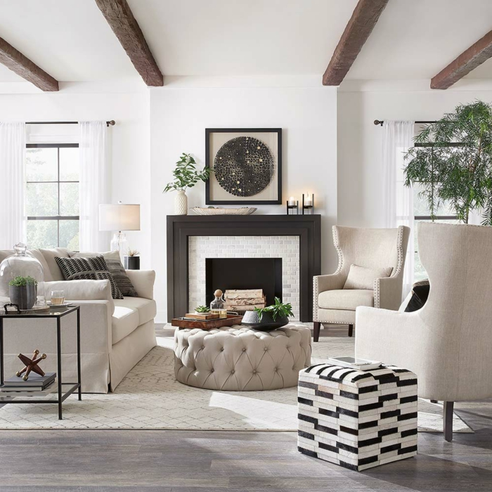joli salon en blanc et gris clair, déco campagne esprit brocante, pouf ottoman, poutres apparentes, plantes vertes, sol et murs blancs