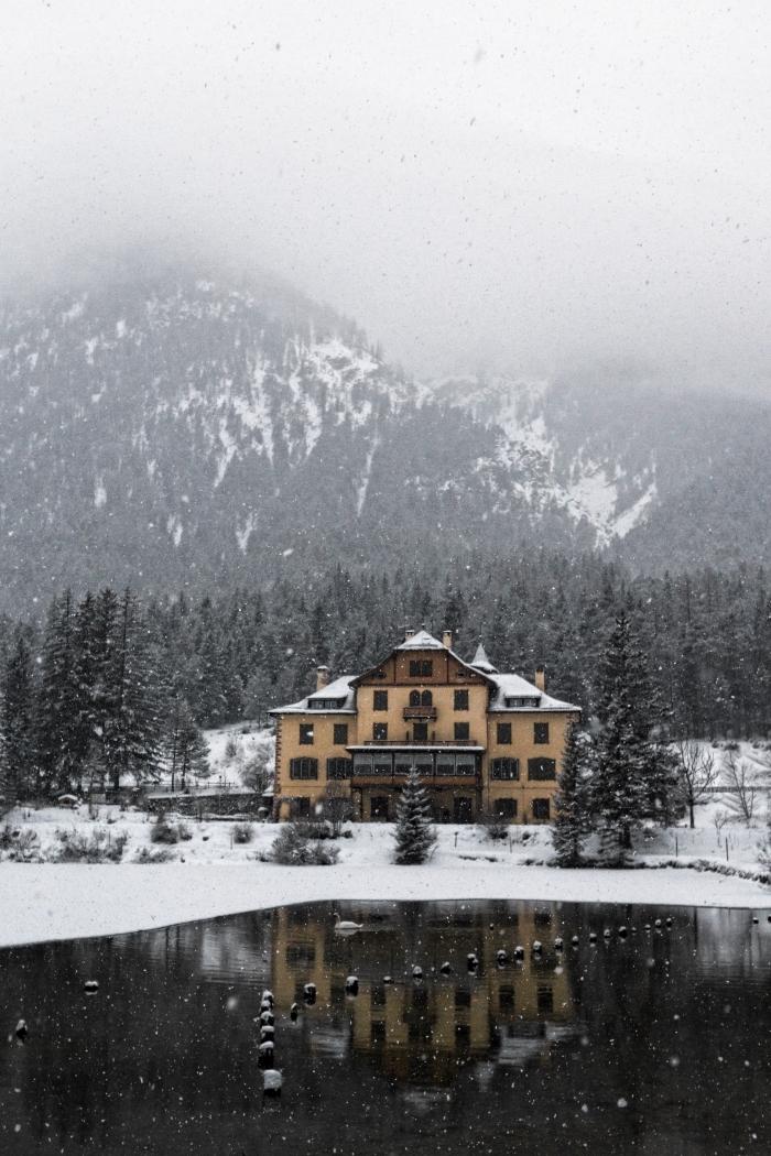 idée image neige qui tombe pour fond d'écran pc, photo de paysage montagnes enneigées et maison au bord de lac