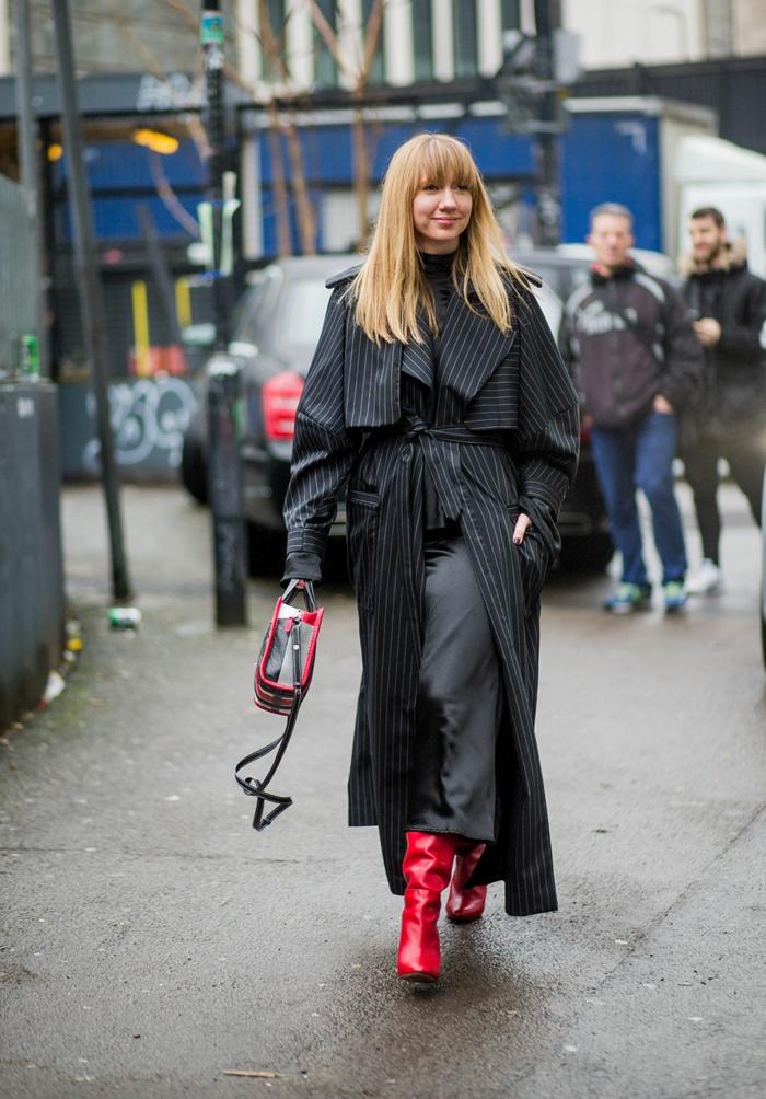 cuissardes rouges, veste longue rayée, sac en noir et rouge, femme aux cheveux blonds, coiffure avec frange