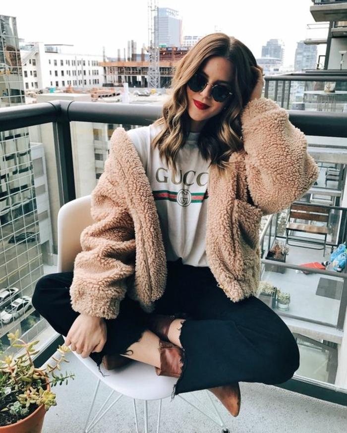 manteau teddy beige, tee-shirt gucci, pantalon noir, femme assise au balcon, bottes marron