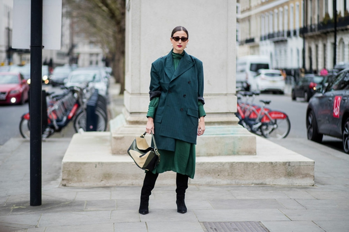 longues bottes noires, manteau vert émeraude, jupe verte, queue de cheval basse