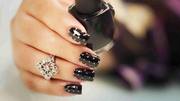 ongles noirs pointillés aux pois blancs, bague à forme géométrique, pierres incrustées