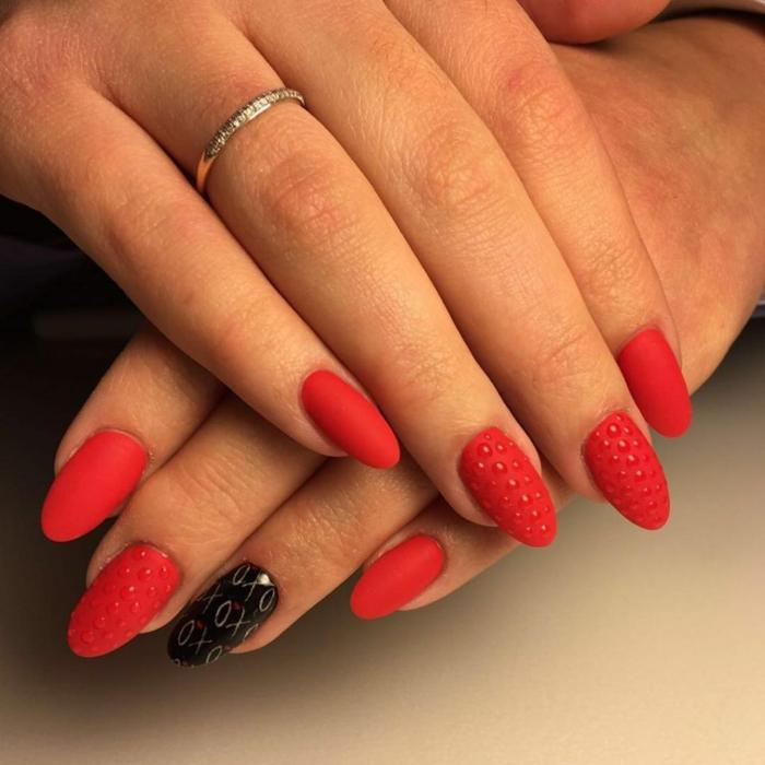 ongles ovales couleur rouge, motifs 3d sur l'ongle, bague fine en métal, ongles mi-longs forme classique