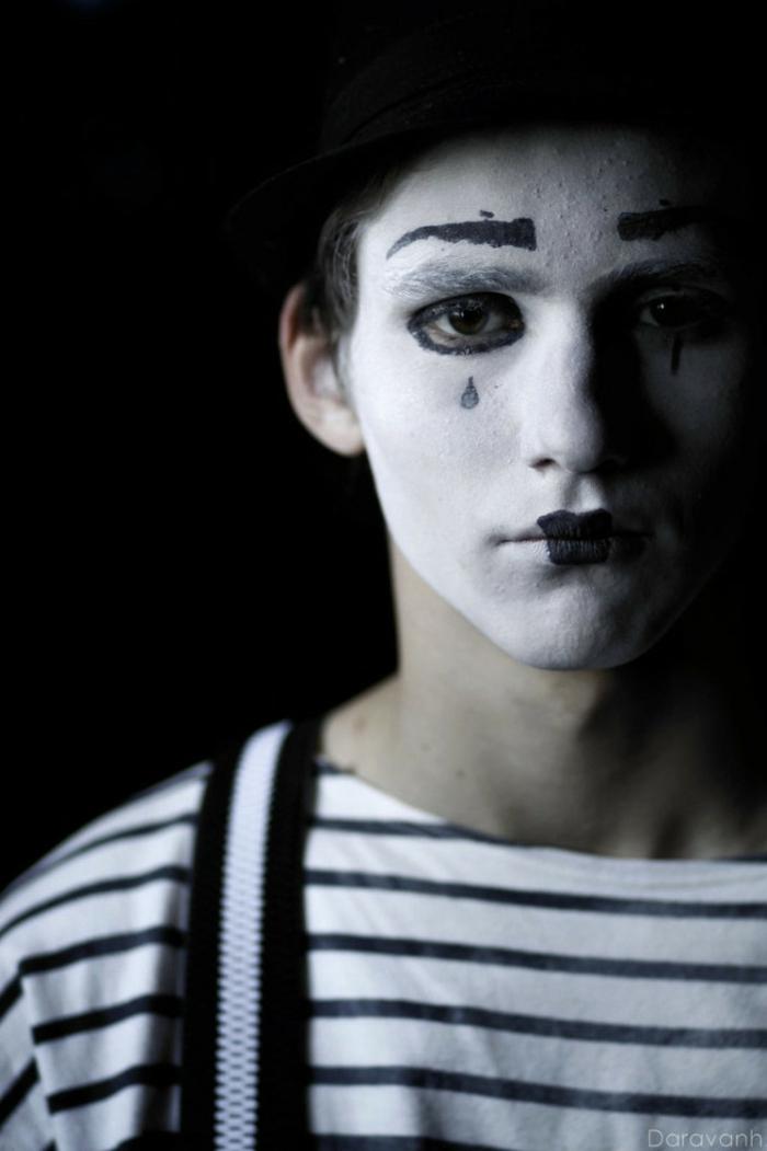 homme en blouse rayée avec un visage de clown, sourcils noirs dessinés, yeux entourés de crayon noir, lèvres peintes