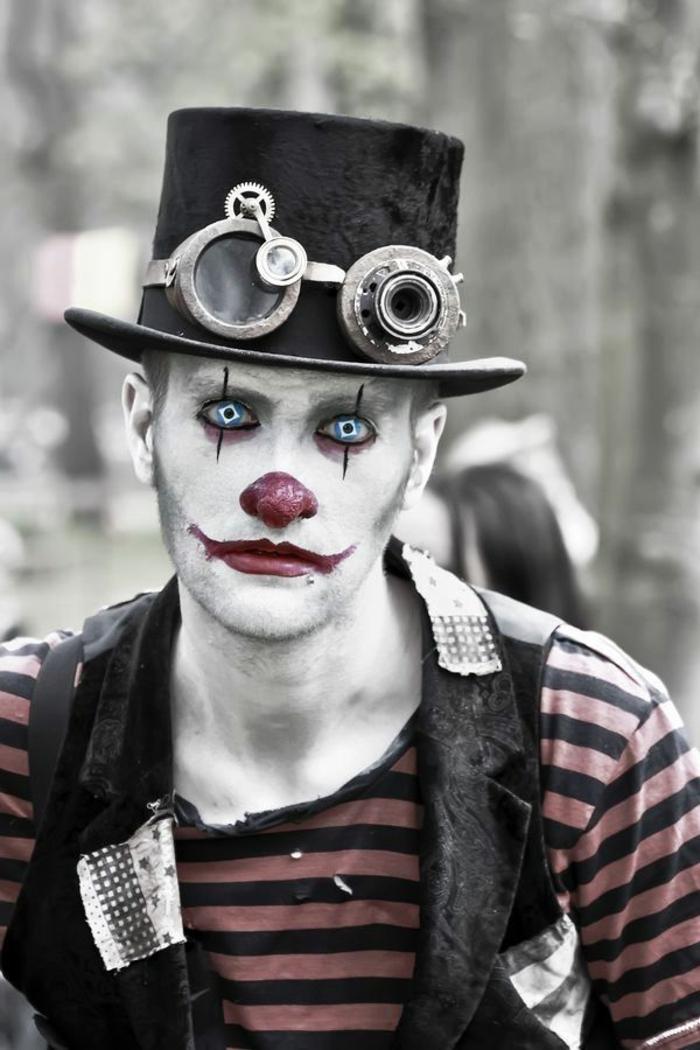 homme maquillé pour halloween, chapeau cylindre et lunettes steampunk, lèvres rouges, nez rouge, lentilles de couleur, blouse rayée