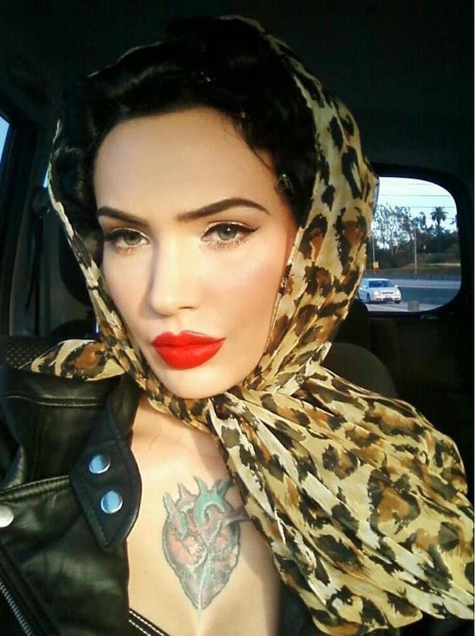 look pin up moderne avec maquillage eye liner et rouge à levres lipstick vif, foulard leopard dans les cheveux, coiffure retro banane et veste cuir biker années 50 et tattoo coeur sur la poitrine