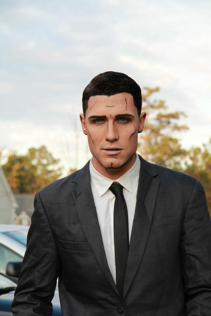 costume noir, chemise blanche et cravate noire, cheveux noirs courts, homme habillé en tenue officielle, visage discrètement maquillé