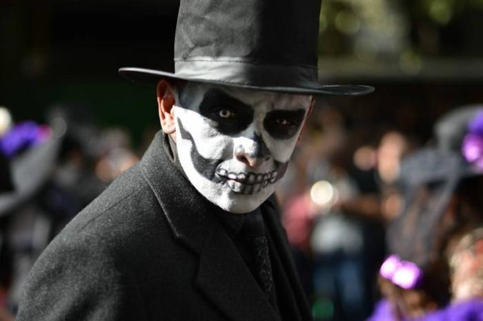 maquillage terrifiant pour halloween, chapeau noir cylindre, dents monstrueuses, cavités oculaires noires, tenue noire