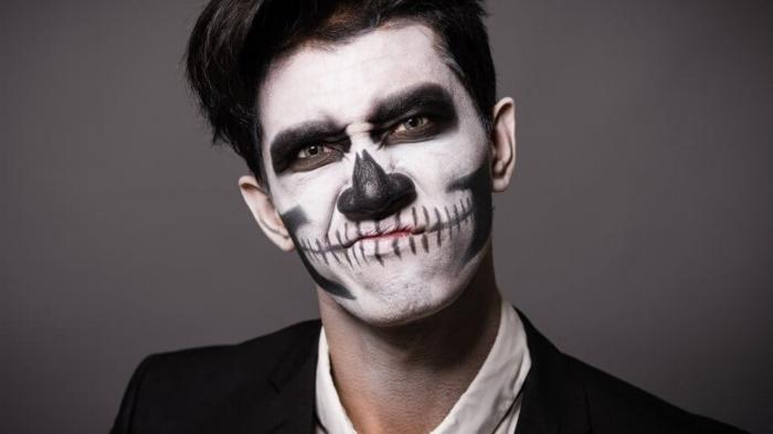 maquillage halloween monochrome, tête de mort créé sur le visage d'un homme avec peintures visage