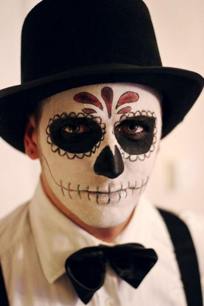 homme déguisé et maquillé pour halloween, lèvres cousues avec marqueur noir, chapeau cylindre, cavités oculaires noires