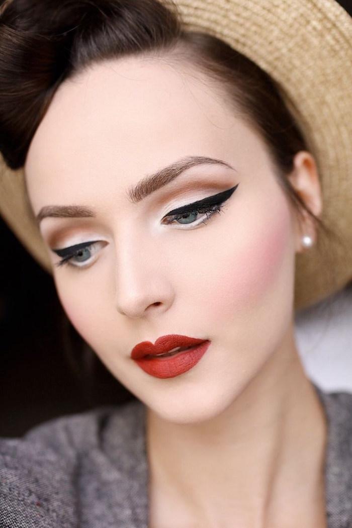 photo visage femme maquillée en pin up avec fond de teint blanc et eyeliner noir et rouge à levres et coiffure retro banane