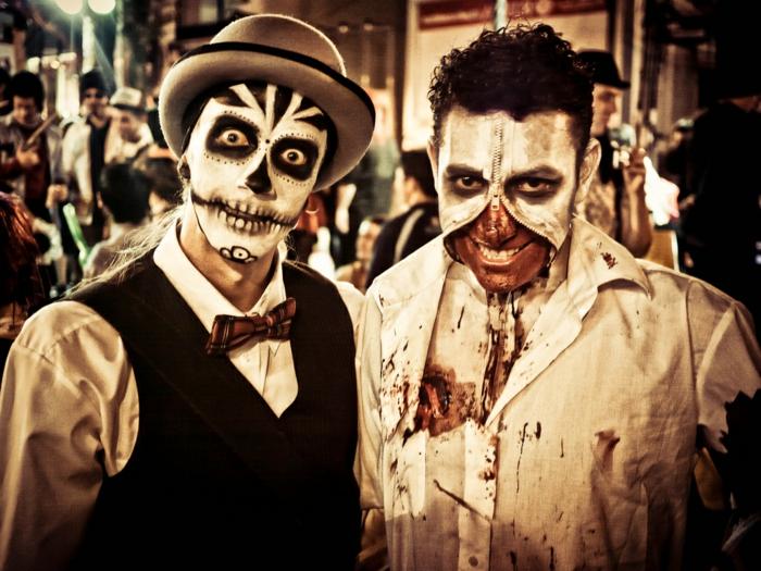 deux hommes maquillés pour halloween, visages blanchis, masque terrifinate zippée, costumes tachés de sang