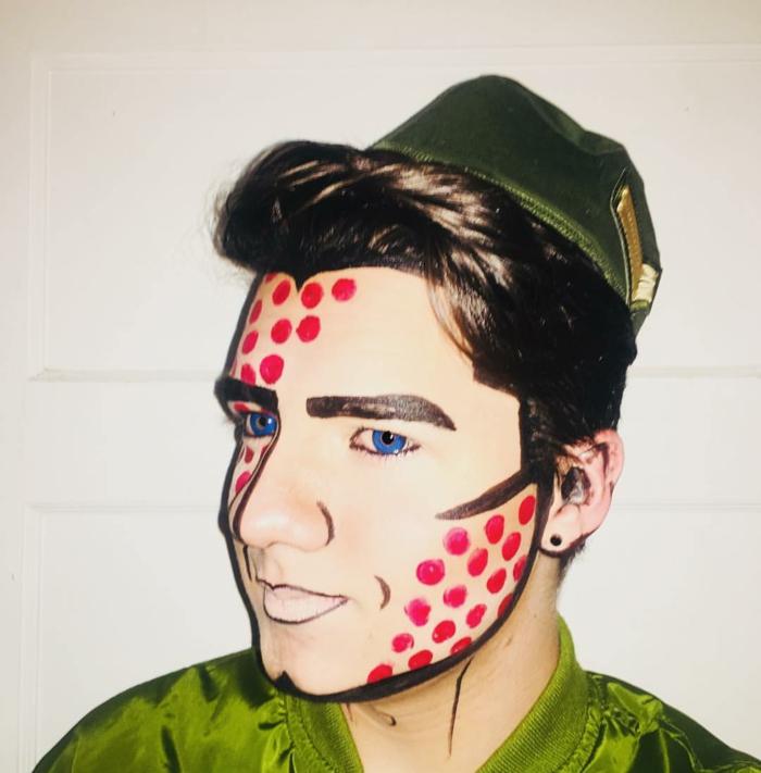 homme au maquillage pop art, chemise verte, pois rouges au visage, lentilles de couleur bleues