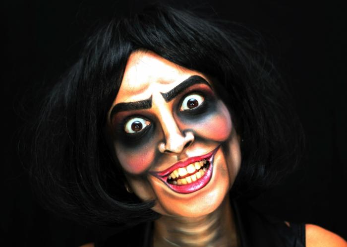 visage maquillé pour halloween, lèvres grottesques peintes roses, sourcils noirs, ombrs noires autour les yeux