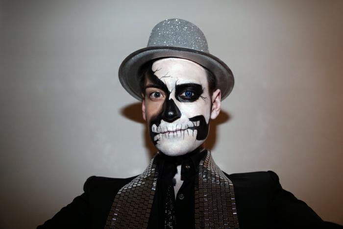 maquillage tête de mort, chapeau gris scintillant, costume noir, maquillage demi tête de mort en noir et blanc