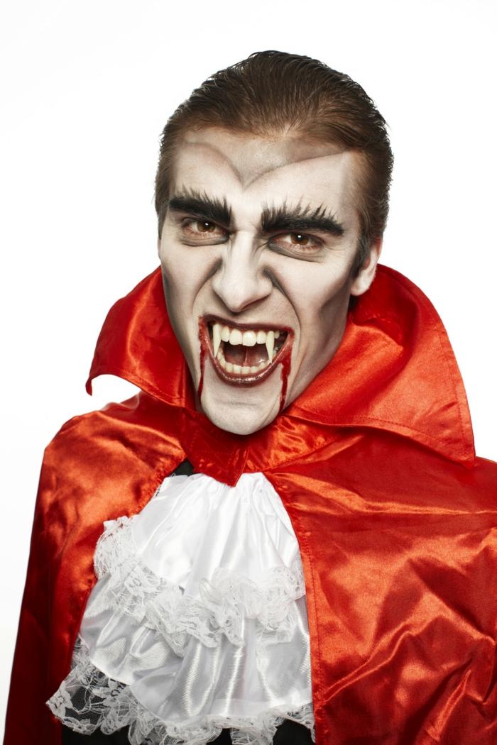 vampire avec des fausses dents de vampire et pèlerine orange, lèvres sanglantes avec faux sang