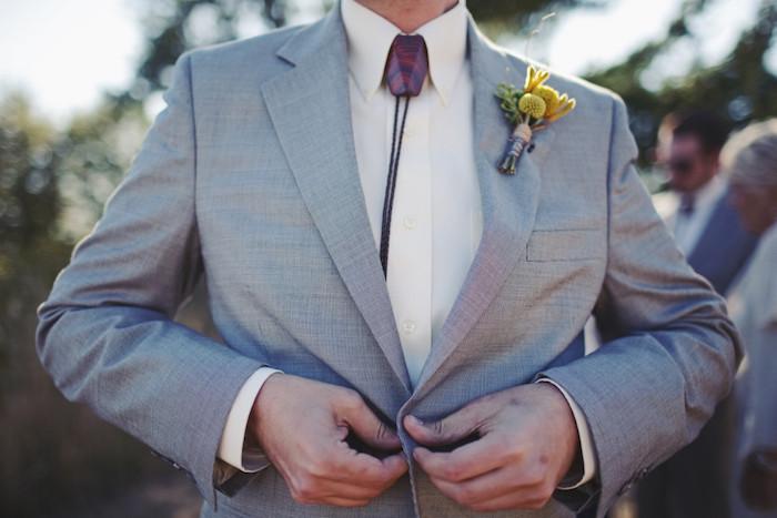 homme en costume gris clair avec collier bolo noir et bijou taillé sur le col de la chemise