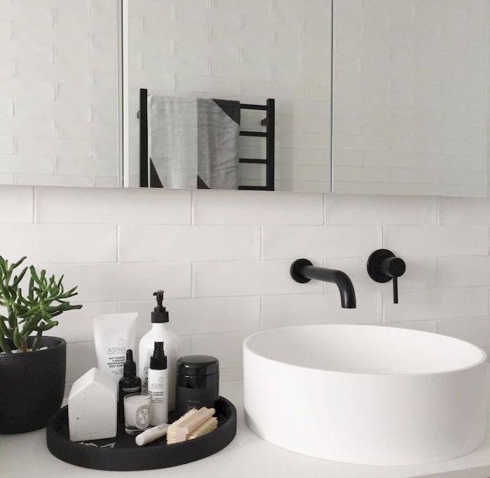 vasque lavabo rond design avec robinetterie noire mat dans salle de bain avec carrelage blanc et grand miroir