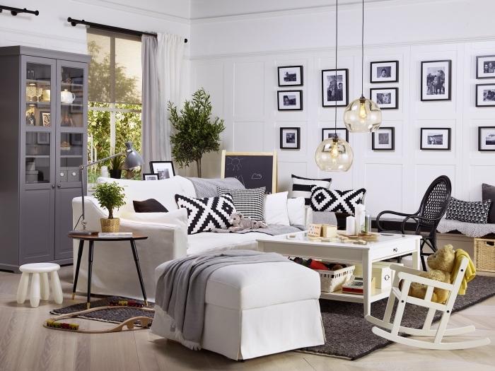 deco salon gris et blanc qui mélange les styles industriel, scandinave et vintage, avec un grand canapé blanc cosy, des accents en bois naturel et un mur de cadres noir et blanc